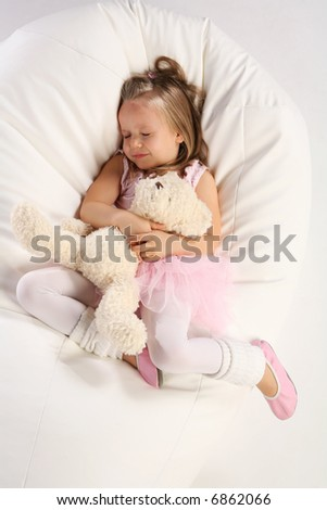 Studio shoot of 4 years old girl sleeping on a large pillow