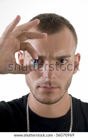Studio shoot of young caucasian man with pill focus on pill - stock photo