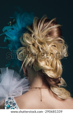 Studio shoot of young woman with creative hairstyle, makeup and dress. Exotic bird - stock photo