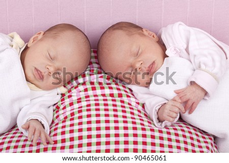 studio-shot a identical ( similar ) baby twin girls sleeping on a pillow.