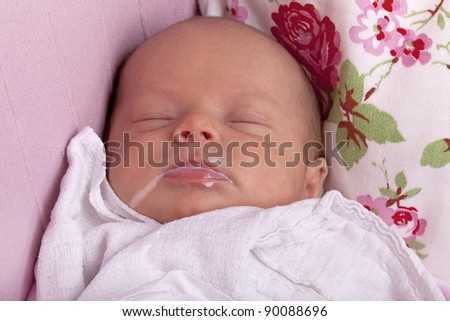 studio-shot of a baby girl sleeping after having milk. milk is running out of the mouth.