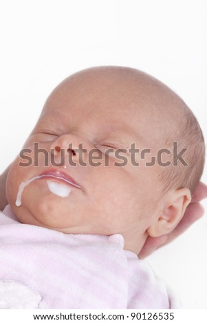 studio-shot of a baby girl sleeping after having milk. milk is running out of the mouth. - stock photo