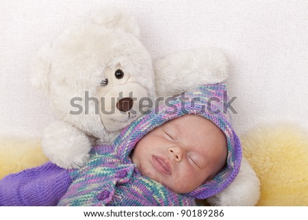 studio-shot of a baby girl sleeping on a  sofa with her teddy bear. baby girl wearing a handmade knitted cardigan.