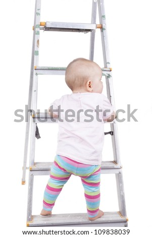 studio-shot of a baby girl standing on a ladder.  concept image for danger, safety, risk and parental responsibility. - stock photo