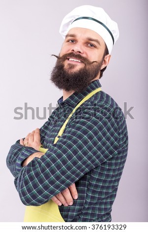 Studio shot of a bearded man with cook hat  holding arms crossed over gray background