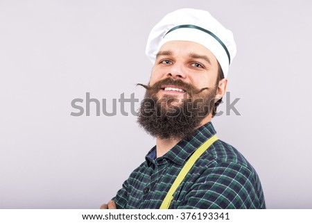 Studio shot of a bearded man with cook hat  over gray background - stock photo