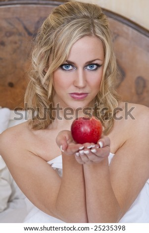 Studio shot of a beautiful blond haired blue eyed female model in bed wrapped in sheets and offering up a tempting red apple