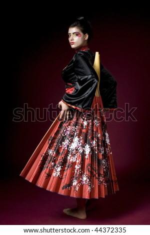 Studio shot of a beautiful geisha covering herself with a big fan - stock photo