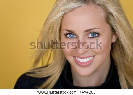 Studio shot of a beautiful young blond woman looking beautiful and happy