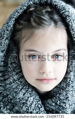 Studio shot of a beautiful young girl in a hooded sweater with shallow depth of field.