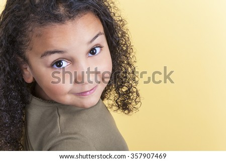 Studio shot of a beautiful young mixed race girl smiling and looking back over her shoulder - stock photo