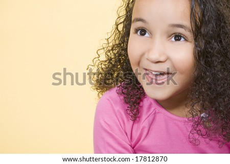 Studio shot of a beautiful young mixed race girl smiling and looking up