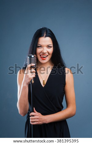 studio shot of a beautiful young singer on dark background