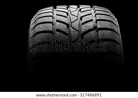 Studio shot of a black car tire in a dark ambient on black background - stock photo