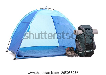 Studio shot of a blue tent, a green rucksack and a pair of boots left next to the tent isolated on white background - stock photo