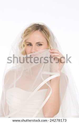 studio shot of a bride isolated on white background playing with the dress veil - stock photo