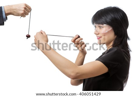 Studio shot of a business female wearing protective  playing conkers