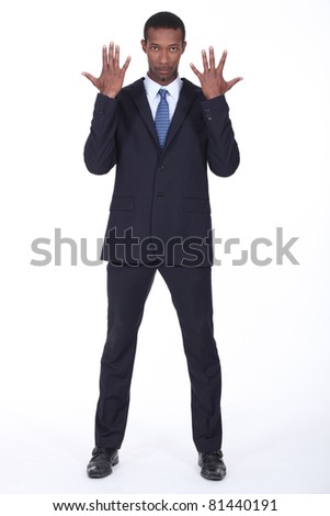Studio shot of a business man with his hands in the air - stock photo