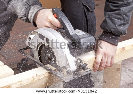 studio-shot of a carpenter cutting wood with electric saw,  for furniture. - stock photo