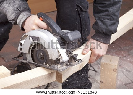 studio-shot of a carpenter cutting wood with electric saw,  for furniture.