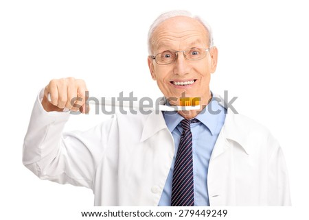 Studio shot of a cheerful mature dentist holding a huge toothbrush and looking at the camera isolated on white background - stock photo