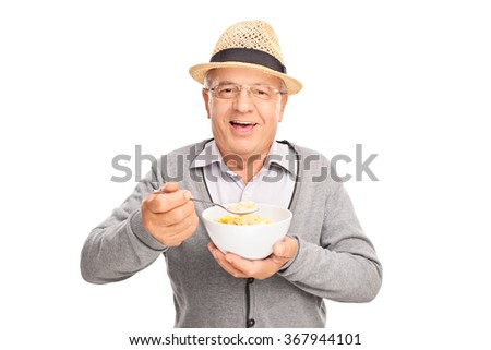 Studio shot of a cheerful senior gentleman eating cereal from a bowl isolated on white background - stock photo