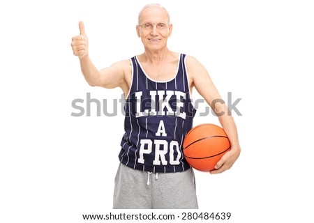 Studio shot of a cheerful senior holding a basketball and giving a thumb up isolated on white background - stock photo