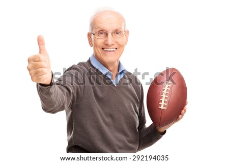 Studio shot of a cheerful senior holding an American football and giving a thumb up isolated on white background - stock photo