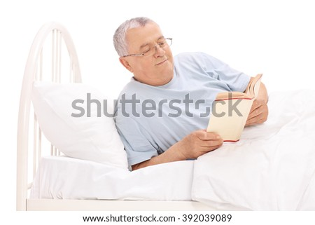 Studio shot of a cheerful senior lying in a bed and reading a book isolated on white background - stock photo