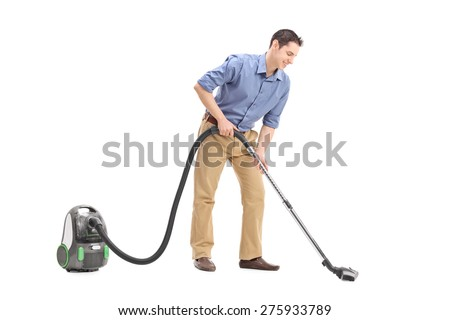 Studio shot of a cheerful young man using a vacuum cleaner isolated on white background - stock photo