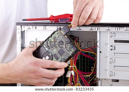 studio-shot of a computer support engineer changing the hard drive of an office computer,isolated on white. - stock photo