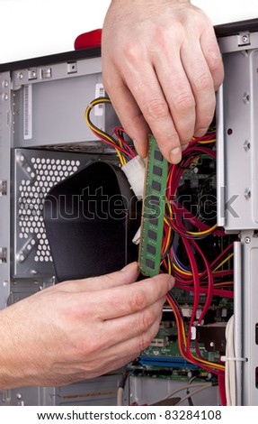 studio-shot of a computer support engineer upgrading the  RAM ( Memory) chip of an office computer,isolated on white - stock photo