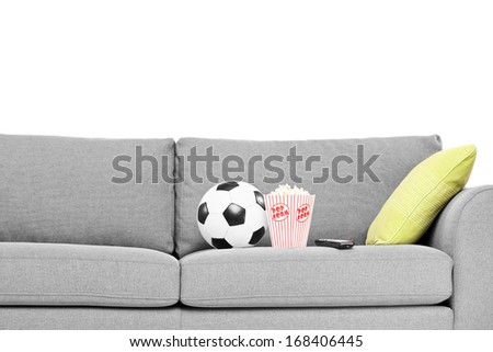Studio shot of a couch with soccer ball and popcorn box on it isolated on white background - stock photo
