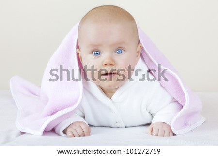 studio-shot of a cute baby girl on bed learning how to crawl. - stock photo