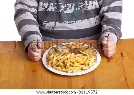 studio-shot of a fat man sitting at a table in the dining room and eating a bunch of steaks and french fries. unhealthy food concept image. - stock photo