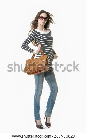 Studio shot of a full body young woman in jeans with sunglasses posing in studio - stock photo