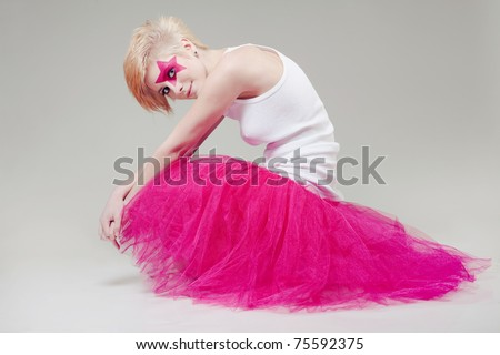 studio shot of a girl with a theatrical makeup and a pink tutu - stock photo