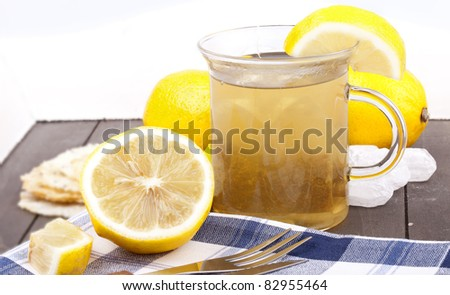 studio-shot of a glass with hot lemon tea, a slice of lemon and rock sugar, on a wooden tray. - stock photo