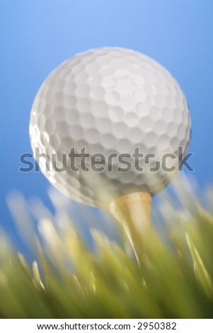 Studio shot of a golfball on a tee in grass. - stock photo
