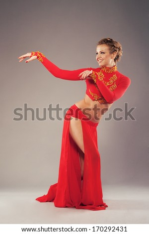 Studio shot of a gorgeous dancer in red clothing - stock photo