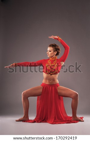 Studio shot of a gorgeous sporty woman in red clothing. Chinese dancing - stock photo