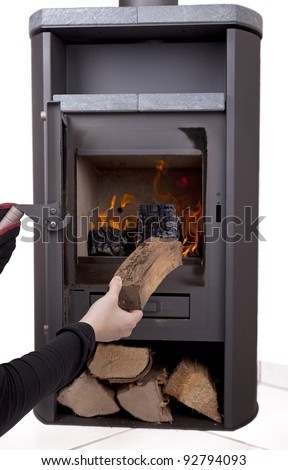 studio-shot of a hand firing a modern wood burning stove with firewood, isolated on a white background. - stock photo
