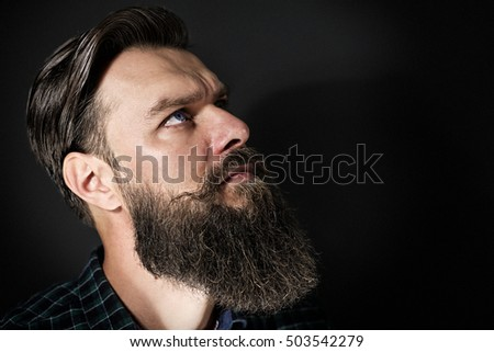Studio shot of a handsome stylish man with beard and mustache
