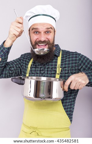 Studio shot of a happy chef tasting soup with a ladle over gray background - stock photo