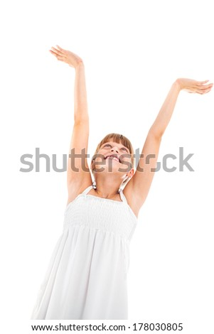 Studio shot of a happy girl with arms up. - stock photo