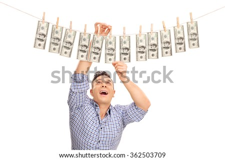 Studio shot of a happy young man pinning money on a clothesline and drying them isolated on white background - stock photo