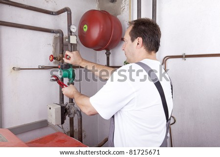 studio-shot of a heating engineer repairing and maintaining the heating system of a single-family house. - stock photo