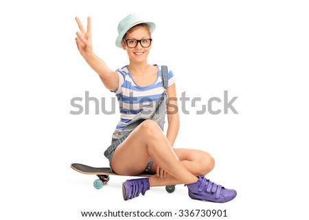 Studio shot of a hipster girl making a peace hand gesture seated on a skateboard isolated on white background - stock photo
