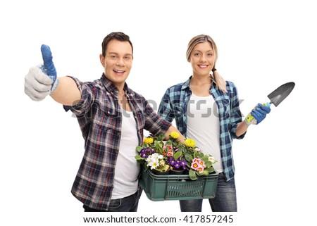 Studio shot of a joyful male and female gardener holding gardening equipment isolated on white background - stock photo