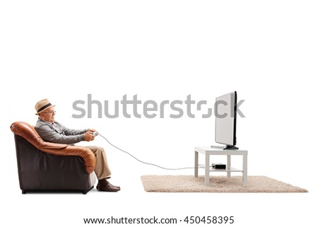Studio shot of a joyful senior playing video games seated on an armchair isolated on white background